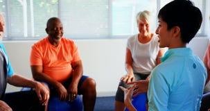 Tylni widok żeńskiego trenera stażowi starszy ludzie w sprawności fizycznej studiu 4k zbiory