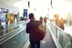 Tylni widok Azjatycki biznesmena odprowadzenie na lotniskowym eskalatorze przy zmierzchem obraz stock