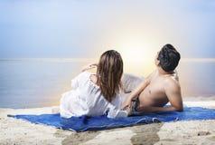 Tylni widok azjatykcia romantyczna para opiera z powrotem na dywanie i patrzeć widoki na ocean w plaży zdjęcie royalty free