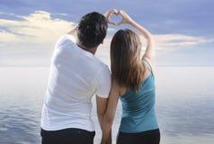 Tylni widok azjatykcia romantyczna para robi sercu kształtuje z palcami na plaży obrazy stock