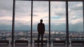Tylni widok biznesmen w biurze z panoramicznym miasto widokiem Biznesmen podziwia miasto od panoramicznego Windows zdjęcia stock