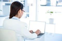 Tylni widok bizneswoman używa laptop Zdjęcie Royalty Free
