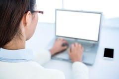 Tylni widok bizneswoman używa laptop Zdjęcia Royalty Free