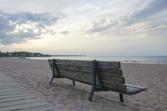Tylni widok drewniana ławka na opustoszałej piaskowatej plaży obrazy stock