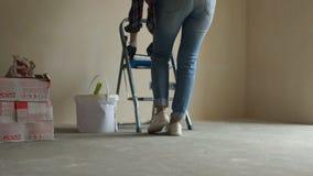 Tylni widok dziewczyny cieki zaczyna naprawia? w jej mieszkaniu, stojaki na stepladder, zaczyna malowa? ?cian? zbiory wideo