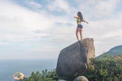 Tylni widok inspirowana sportsmenki pozycja na skale w górach z jej rękami szeroko rozpościerać podziwiać chmurnego zdjęcie stock
