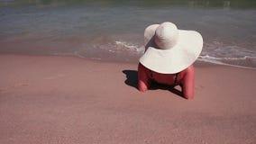 Tylni widok kobieta w białym słońce kapeluszu i bikini podczas gdy sunbathing na dennej piaska raju plaży zdjęcie wideo