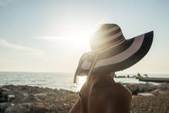 Tylni widok kobieta w swimsuit przy plażowym dopatrywanie zmierzchem Fotografia Stock