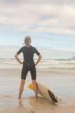 Tylni widok kobieta z ręką na modnej pozyci surfboard na brzeg Fotografia Stock