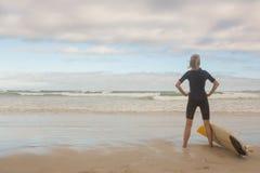 Tylni widok kobieta z ręką na modnej pozyci surfboarda przeciw chmurnemu niebu zdjęcia royalty free