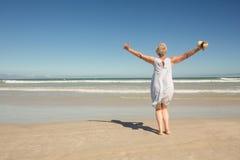 Tylni widok kobiety pozycja na piasku przeciw jasnemu niebu Zdjęcie Royalty Free