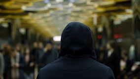Tylni widok mężczyzna z zmrokiem - błękitny hoodie na pozycji przed tłumem przy stacją, oporu pojęcie z bliska fotografia royalty free