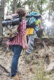 Tylni widok mężczyzna dopatrywania żeńskiego wycieczkowicza wspinaczkowa faleza w lesie Fotografia Stock
