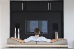 Tylni widok mężczyzna dopatrywania telewizja Obraz Royalty Free