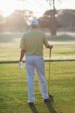 Tylni widok mężczyzna mienia kij golfowy Fotografia Stock