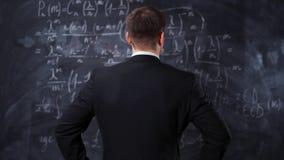 Tylni widok mężczyzna przeciw chalkboard z matematyki formuły równaniami zbiory