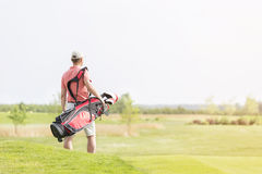 Tylni widok mężczyzna przewożenia kija golfowego torba podczas gdy chodzący przy kursem Zdjęcia Royalty Free
