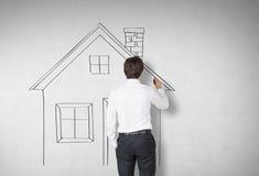Tylni widok mężczyzna rysuje dom na betonie Obraz Stock