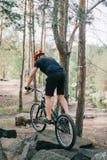 tylni widok męski próbny rowerzysta w ochronnej hełm jazdie na halnym bicyklu na kamieniach obraz stock