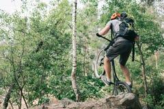 tylni widok męski próbny rowerzysta w ochronnym hełma równoważeniu na tylnym kole rower górski fotografia royalty free