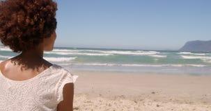 Tylni widok młoda amerykanin afrykańskiego pochodzenia kobieta relaksuje na plaży w świetle słonecznym 4k zbiory