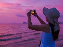 Tylni widok młoda kobieta robi obrazkowi na komórka telefonu kamerze obrazy royalty free
