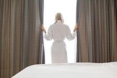 Tylni widok młoda kobieta w bathrobe otwarcia nadokiennych zasłonach przy pokojem hotelowym Fotografia Stock