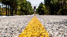 Tylni widok młoda kobieta z rękami w górę odprowadzenia wzdłuż żółtej linii podziału pusta droga wśród lasu Obrazy Royalty Free