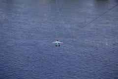 Tylni widok młody człowiek jazda na zamek błyskawiczny linii przeciw tłu błękitna wody rzecznej fala fotografia stock