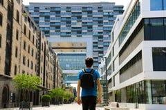 Tylni widok młody człowiek z plecakiem właśnie przyjeżdżał w dużym mieście i patrzeć nowożytni budynki z perspektywami i obraz stock