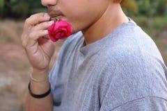 Tylni widok młody romantyczny mężczyzna trzyma czerwieni róży w jego usta na natura zamazującym tle Miłości i romans walentynki ` Obrazy Royalty Free