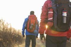 Tylni widok męscy backpackers chodzi w polu Zdjęcia Royalty Free