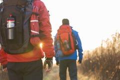 Tylni widok męscy backpackers chodzi w polu Obraz Royalty Free