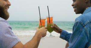 Tylni widok Mieszana biegowa para wznosi toast koktajlu napój na plaży 4k zbiory wideo