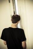 Tylni widok nastoletni chłopak Oparta głowa Przeciw ścianie zdjęcia stock