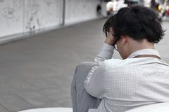 Tylni widok niespokojny zapracowany młody Azjatycki biznesowego mężczyzny obsiadanie i wzruszający czoło z rękami fotografia royalty free