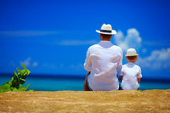 Tylni widok ojciec i syn siedzi wpólnie na niebo horyzoncie Obraz Royalty Free