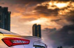 Tylni widok parkujący w mieście blisko wysokiego budynku samochód po tym jak deszcz, chmury i i wodną kropelkę popielatym i pomar Obrazy Stock