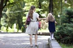 Tylni widok potomstwa matkuje odprowadzenie z małej dziewczynki córką wewnątrz Fotografia Stock