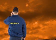 Tylni widok pracownik ochrony przeciw chmurnemu niebu podczas zmierzchu Zdjęcie Stock
