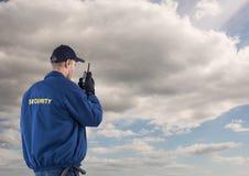 Tylni widok pracownik ochrony używa radio przeciw chmurnemu niebu Zdjęcia Royalty Free