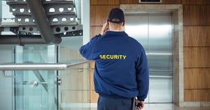Tylni widok pracownika ochrony czekanie dla dźwignięcia podczas gdy stojący w budynku biurowym Obrazy Stock
