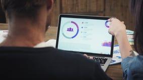 Tylni widok pracuje z laptopem młody człowiek podczas gdy siedzący przy biurkiem w kreatywnie biurze zbiory