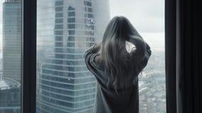 Tylni widok przy Piękną blondynki kobietą stoi patrzeć z długiego okno luksusowy nowożytny mieszkanie lub pokój hotelowy zbiory wideo