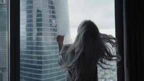 Tylni widok przy Piękną blondynki kobietą stoi patrzeć z długiego okno luksusowy nowożytny mieszkanie lub pokój hotelowy zbiory