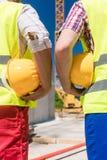 Tylni widok ręki dwa pracownika trzyma żółtych ciężkich kapelusze Fotografia Royalty Free