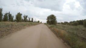 Tylni widok samochodowy jeżdżenie wzdłuż wiejskiej drogi gruntowej zbiory