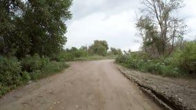 Tylni widok samochodowy jeżdżenie wzdłuż wiejskiej drogi gruntowej zdjęcie wideo
