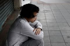 Tylni widok sfrustowany skołowany młody Azjatycki biznesowy mężczyzna siedzi jego kolana i ściska do klatki piersiowej Zdjęcie Stock