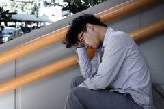 Tylni widok sfrustowany zaakcentowany młody Azjatycki biznesowego mężczyzna siedzący schody biuro i uczucie próbujący lub wyczerp obrazy royalty free